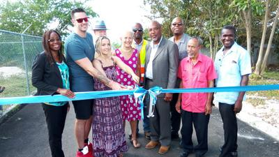 Photo shows.. USA couple Robert and Chelsea Pearson, cutting the ribbon to the newly paved roadway in Blacks Bay, Belmont Westmoreland, which they financed at the tune of over Jamaican $7,000,000 , the couple is seen here being flocked by Principal Of the Bluefields Basic School, Joy Baker (at left)  and Member of Parliament for Eastern Westmoreland, Luthur Buchanan, Council Valence Gifford and other members of the Bluefields Environmental and Protection Association (at right) .